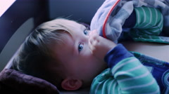 Adorable baby boy laying on a changing table with a pacifier in his mouth Stock Footage