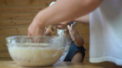 Little baby boy helps mother at the kitchen Stock Footage