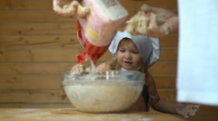 Little baby master chef covered with flour cooking with mother Stock Footage