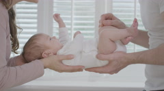 4K New parents holding baby daughter next to window in natural light Stock Footage