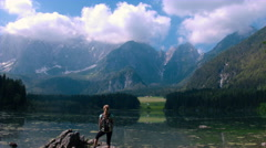 Aerial - Moving above female hiker standing at lake shore and looking at view Stock Footage