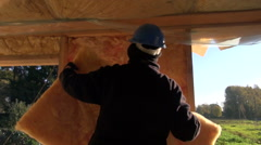 Builder with a safety hat insulating house frame Stock Footage