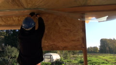 Builder with protective hat insulating house Stock Footage