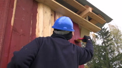 Builder wearing safety hat painting farm house Stock Footage