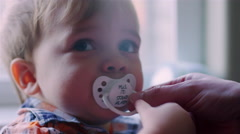 Baby boy, mom takes his pacifier out and sets him on the ground Stock Footage