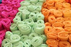 Many rolls of colored felt for sale in the market stall of fabrics Stock Photos