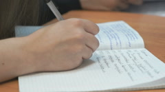 Schoolgirl writes in copybook at the lesson Stock Footage