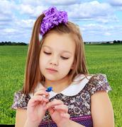 Beautiful little girl looking at blue flower Stock Photos