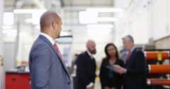 4K Portrait smiling businessman in factory with colleagues in background Stock Footage