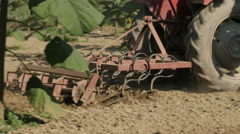 Tractor cultivating soil at trees plantation,close up by Sheyno. Stock Footage