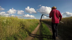 Man in fields walking with scythe, 4K Stock Footage