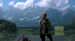 Jib shot - Young female hiker with a backpack standing at the shore of a lake Stock Footage