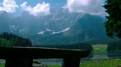 Wood bench made of logs at the lake shore with Alpine mountains in the backgroun Stock Footage