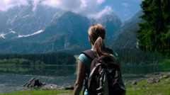 Young female hiker with a backpack arriving to the lake in the mountains Stock Footage