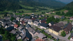 Aerial - Flying away from a small rural village beneath the Alpine mountain Stock Footage