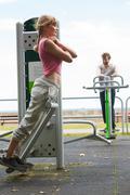 Active woman exercising on backtrainer outdoor. Stock Photos