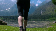 Hiking - Closeup of a female legs walking in the mountains arriving to the lake Stock Footage