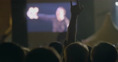 Spectator man showing a rock, devil horns gesture in front of big screen at Stock Footage