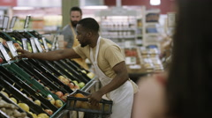 4K Cheerful coworkers in grocery store stocking shelves Stock Footage