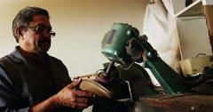 Shoemaker polishing a shoe with machine Stock Footage