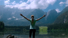 Jib shot - Fit female sport model standing near the lake with arms outstretched Stock Footage