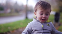 Adorable little boy walking toward the camera in a park Stock Footage
