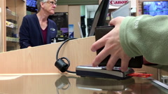 Woan paying Tangerine credit card to buy camera Stock Footage