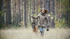 Young cute happy woman plays with her dog - german shepherd in yellow autumn Stock Footage