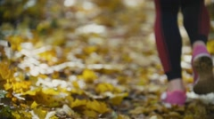 Female Legs Feet Running at yellow autumn park. Sports lifestyle concept, slow Stock Footage