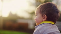 Close up of the back of a little boy's head, sitting outside Stock Footage