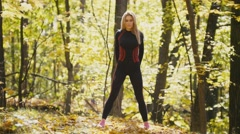 Woman doing fitness exercises outdoor. Female stretching her loin in autumn Stock Footage