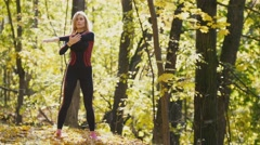 Woman doing fitness exercises outdoor. Female stretching her arms in autumn Stock Footage