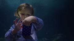 Little Boy Swipes Through Photos On Smartphone, Turns To Watch Sharks In Tank Stock Footage