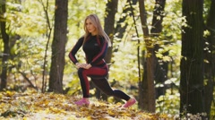 Woman doing fitness exercises outdoor. Female stretching in autumn forest. Slim Stock Footage
