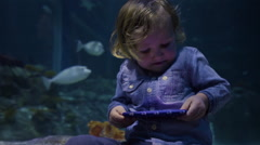 2 Year Old Little Boy Takes Selfies, Looks At Photos, In Front Of Aquarium Tank Stock Footage