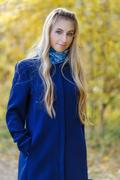 Girl in a Blue Coat in the yellow autumn background Stock Photos