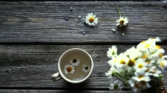Tea with chamomile. Bouquet with daisies on a wooden background. Stock Footage