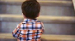 Little boy standing at the bottom of stairs, holding a sippy cup Stock Footage