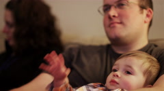 Close up of a little boy sitting on his father's lap and watching television Stock Footage