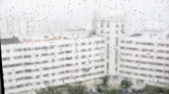 Raindrops running down a window glass in the rain Stock Footage