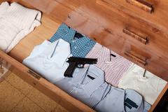 Gun hidden in a drawer full of shirt at home Stock Photos