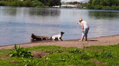Visitor playing with pet dog in Loch Leven, Kinross, Scotland, UK Stock Footage