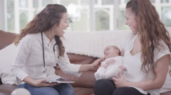 4K New mother with baby daughter talking to health visitor at home Stock Footage