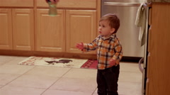 Little boy in a kitchen gets a sippy cup handed to him and walks out Stock Footage