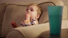 Little boy sitting on the couch eating a snack and watching television Stock Footage