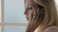 Business woman looking through a window and talking on a cell phone. Stock Footage