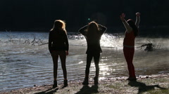 Athletic girls sports in morning sunrise light near to the mountain lake Stock Footage