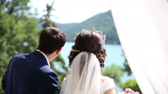 The bride and groom are looking at lake Stock Footage