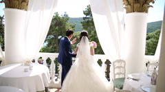The bride and groom are standing on the balcony and look at the lake Stock Footage
