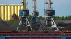 Three Crane Load Coal Into a Barge the Day in the Background, Piles of Coal and Stock Footage